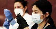 Сотрудники центра массовой вакцинации против коронавируса в масках готовят инъекции