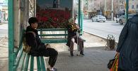 Люди сидят на автобусной остановке
