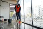 Работник коммунальной службы проводит уборку теплой остановки
