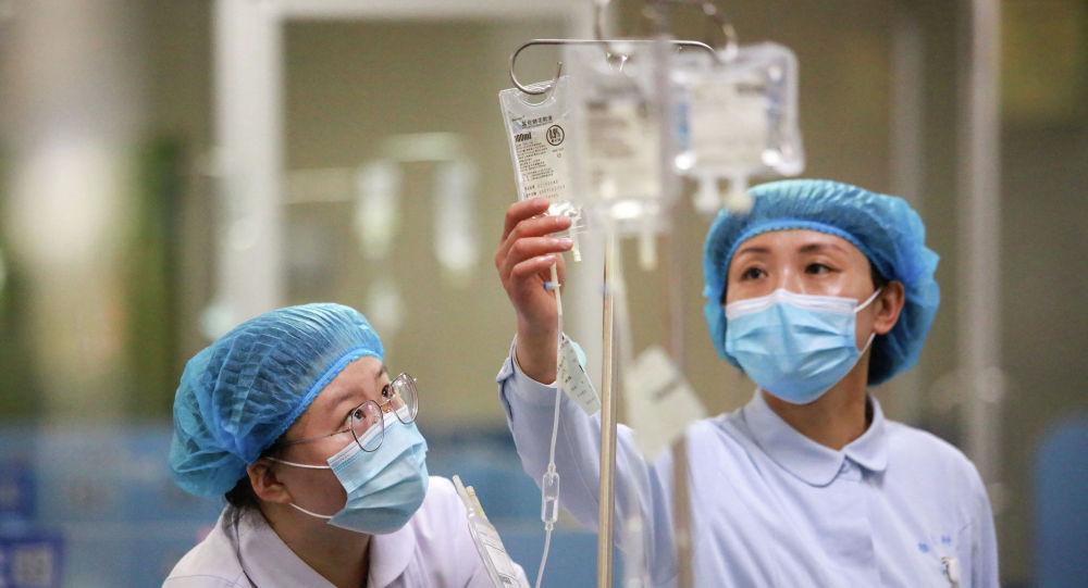 Медсестры в защитных костюмах поправляют капельницы в больнице с коронавирусом