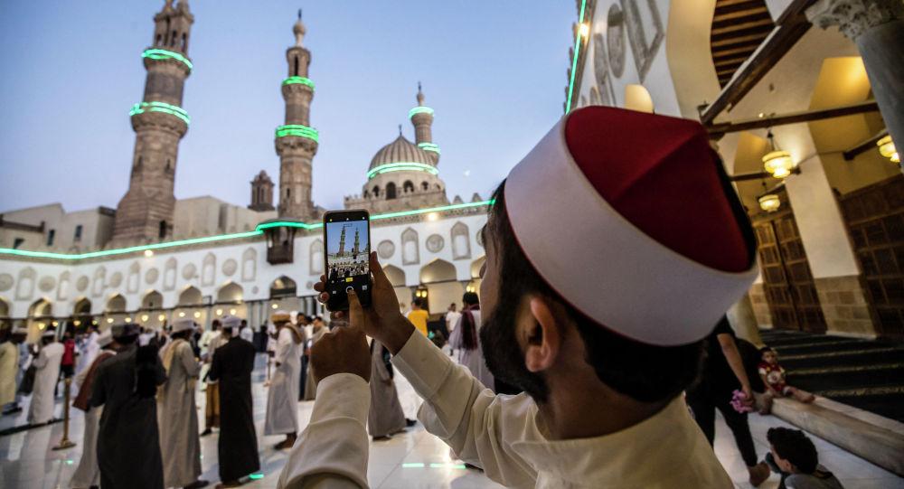 Мусульманин фотографирует праздничную подсветку минаретов церкви перед началом массовой молитвы после завершения священного месяца Рамазан