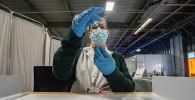 Медсестра набирает в шприц вакцину от коронавируса