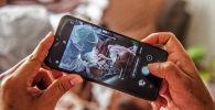 Человек снимает на смартфон, как врач осматривает пациента с коронавирусом
