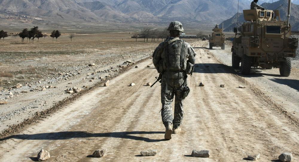 Американский солдат идет по строящейся дороге возле Баграма, примерно в 60 км от Кабула, Афганистан