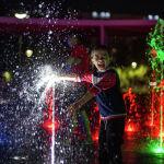 Ребенок радуется возможности играть с фонтаном