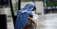 Мужчина в маске укрывается зонтом во время сильного ветра