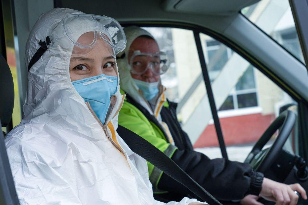 Медики в защитных костюмах выезжают на вызов на машине скорой помощи
