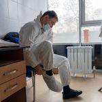 Медик надевает защитный костюм перед началом смены в больнице с коронавирусом