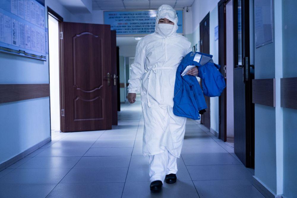 Медик в защитном костюме идет по коридору больницы