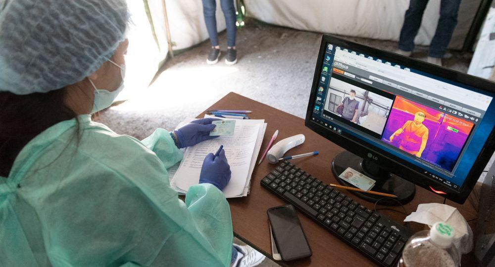 Медик следит за монитором температуры в передвижном пункте вакцинации от коронавируса