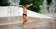 Мальчик купается в фонтане в жару