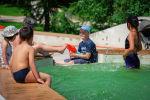Дети играют в фонтане в летнюю жару