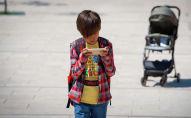 Мальчик идет по улице с телефоном в руках