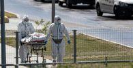 Медики в защитных костюмах везут пациента в больницу с коронавирусом