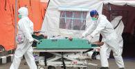 Медики в защитных костюмах везут на носилках пациента с коронавирусом