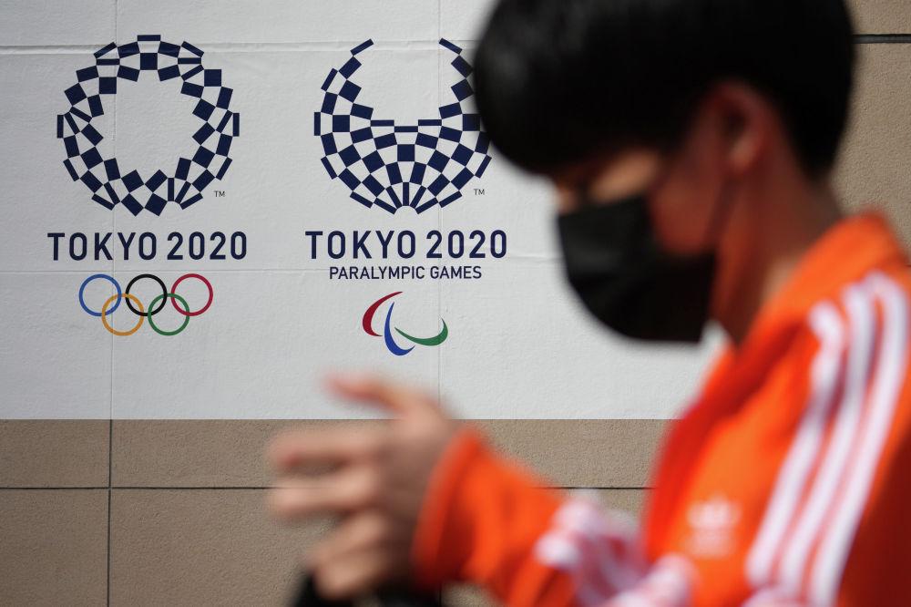 Мальчик в маске проходит мимо логотипов Олимпиады в Токио