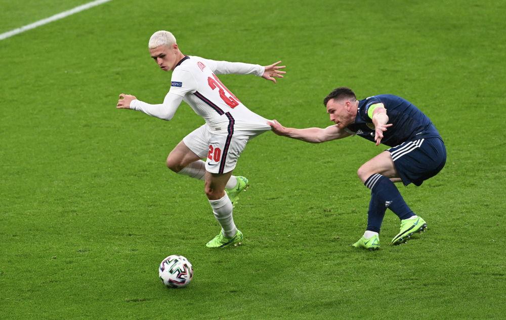 Англия құррамасының футболшысы Фил Фоденнің шотландиялық Эндрю Робертсонмен тартысы.