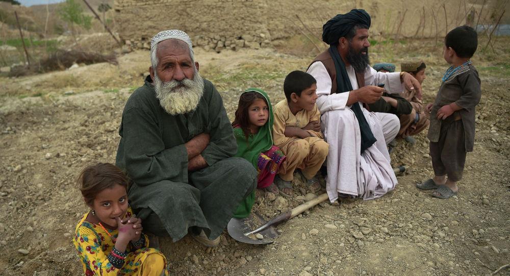 Мужчины и дети сидят перед своим домом. В центре территории, осажденной талибами, одна из самых важных плотин гидроэлектростанций Афганистана