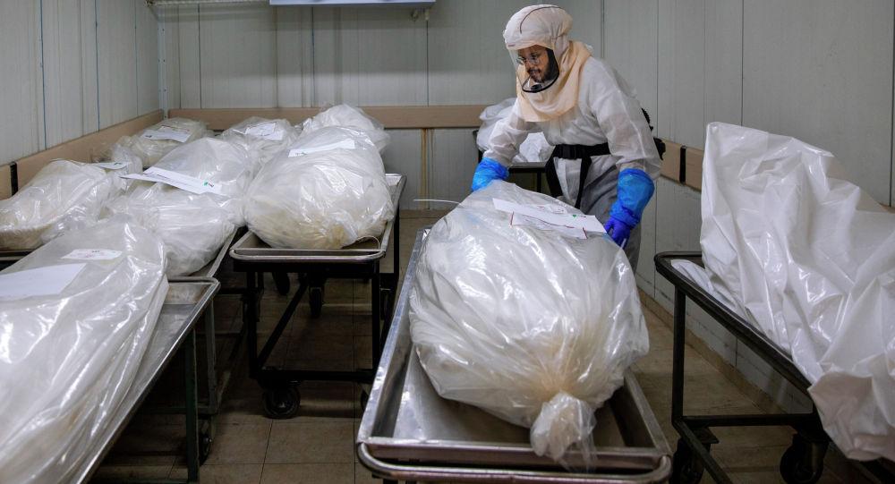 Работник морга упаковывает тела погибших от коронавируса