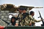 афганские полицейские сидят на бронетранспортере на блокпосту в районе Панджвай провинции Кандагар после того, как талибы захватили ключевой район в их бывшем бастионе Кандагар после ожесточенных ночных боев с афганцами.