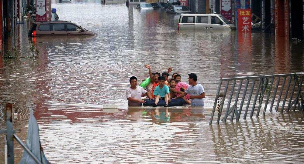 Взрослые перевозят детей на надувном матрасе в затопленном после наводнения городском районе в Китае