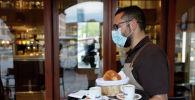 Официант в маске несет заказ посетителям кафе