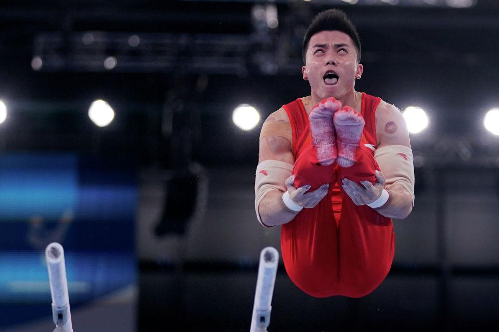 Китайский гимнаст Лин Чаопян совершает соскок с брусьев