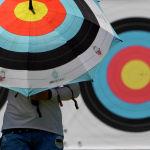 Стрелок из лука прогуливается под зонтом с изображением мишени на Олимпиаде в Токио