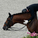 Бразильский конник Жоао Виктор Маркари Олива разговаривает со своим скакуном после соревнований по выездке