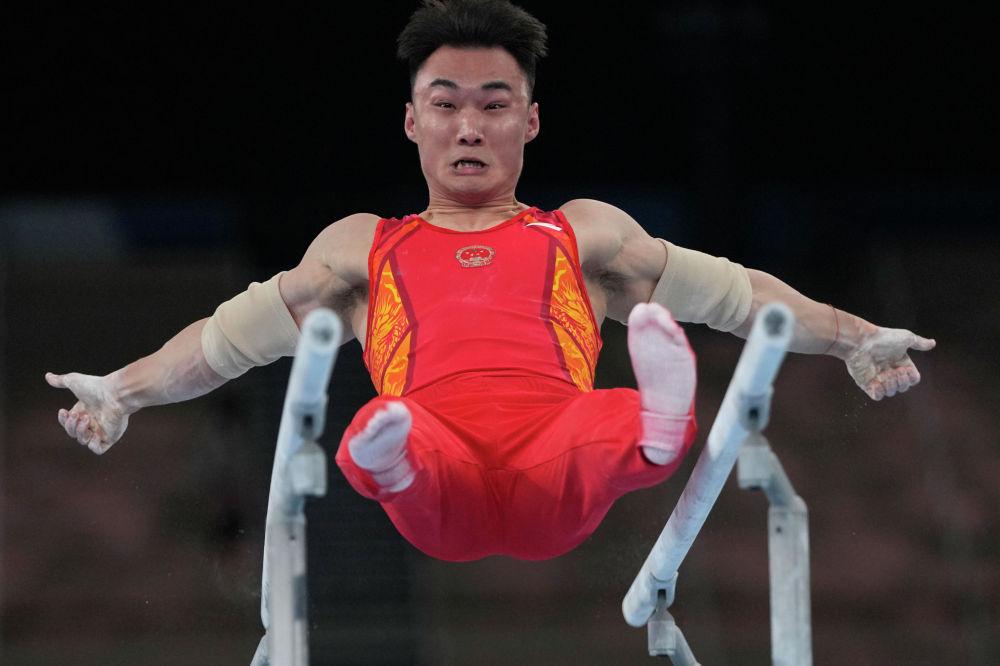 Китайский гимнаст Сун Вей выступает в упражнении на брусьях на Олимпиаде