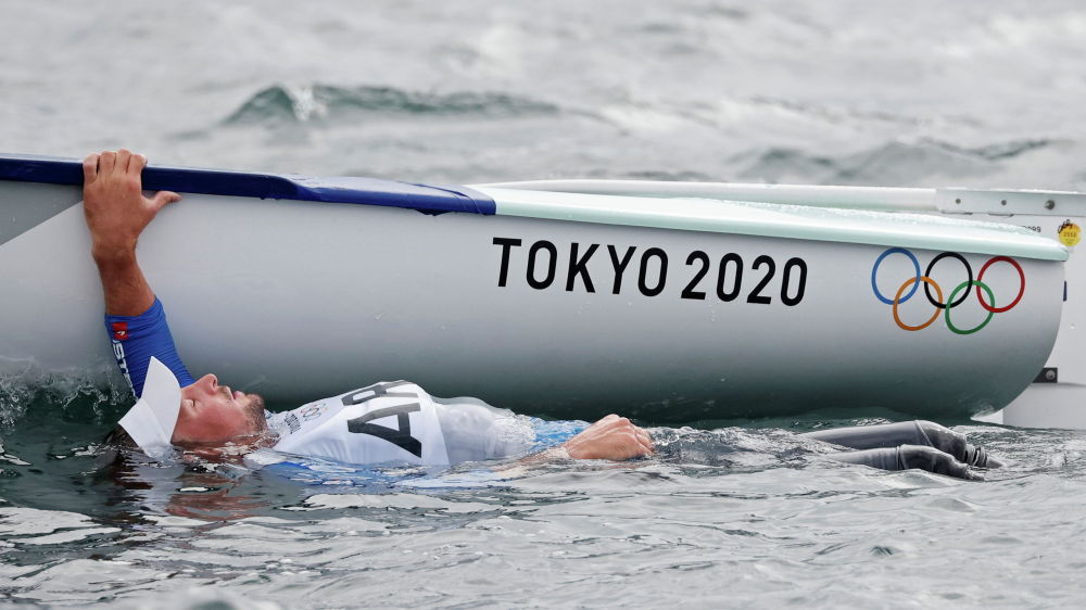 Факундо Олецца из Аргентины плывет за бортом своей лодки после соревнований по парусному спорту на Олимпиаде