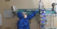 Медсестра в защитном костюме работает с аппаратурой в реанимации больницы с коронавирусом