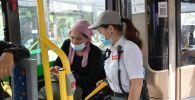 Кондуктор и пассажир в автобусе в Нур-Султане