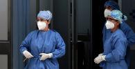 Медики в защи тных костюмах готовятся принять пациента на скорой в больнице с коронавирусом