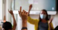 Ученики на уроке поднимают руки, чтобы ответить учителю