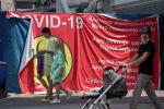 Люди без масок проходят мимо предупреждающих об опасности коронавируса плакатов