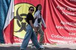 Девушки без масок проходят мимо плаката, предупреждающего об опасности коронавируса