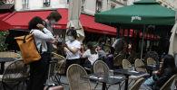 Сотрудник кафе в маске проверяет статус посетителей с помощью телефона