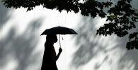Девушка в маске идет под зонтом по улице
