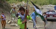 Афганский подросток в Панджшере размахивает флагом страны, надетым на ружье