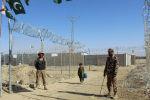 Афганский мальчик проходит мимо пакистанских военных, охраняющих границу между странами