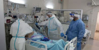 Врачи работают с пациентом в отделении интенсивной терапии в больнице с коронавирусом
