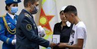 Министр обороны Нурлан Ермекбаев вручает награды семьям погибших близ Тараза военных