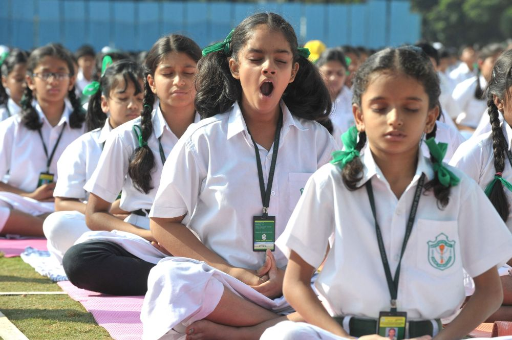Индийская девочка зевает во время занятия йогой в школе.