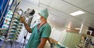 Медик следит за аппаратурой в отделении реанимации в больнице с коронавирусом