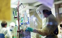 Медик в защитном костюме проверяет апааратуру в отделении реанимации в больице с коронавирусом