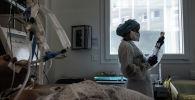 Медсестра в защитном костюме готовит лекарства для капельницы пациенту в палате реанимации больницы с коронавирусом