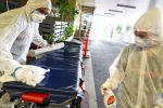Медики в защитных костюмах дезинфицируют каталку из машины скорой помощи