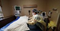 Медик передвигает тело погибшего от коронавируса пациента для транспортировки в морг