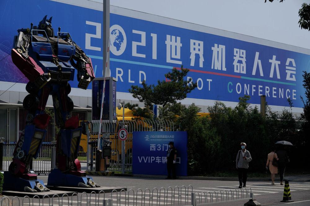 Мужчина в маске проходит мимо Всемирной конференции роботов, проходящей в Пекине, Китай, в пятницу, 10 сентября 2021 г. (AP Photo / Ng Han Guan)